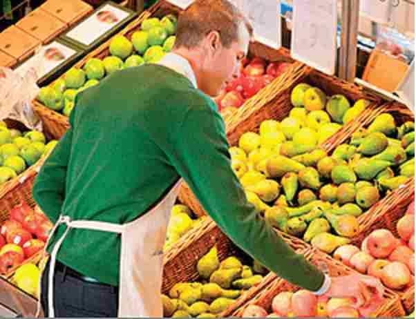 Bild på en herre inom som står bland frukt som symboliserar garageportar inom detaljhandel